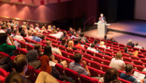 Photograph of an auditorium, with an audience watching a presentation by a speaker at a lectern